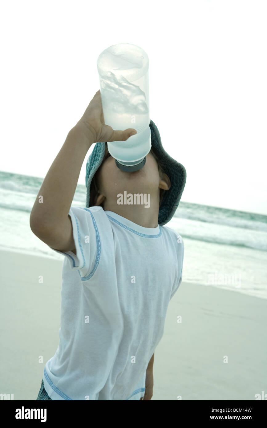Boy drinking from water bottle on beach, head back - Stock Image