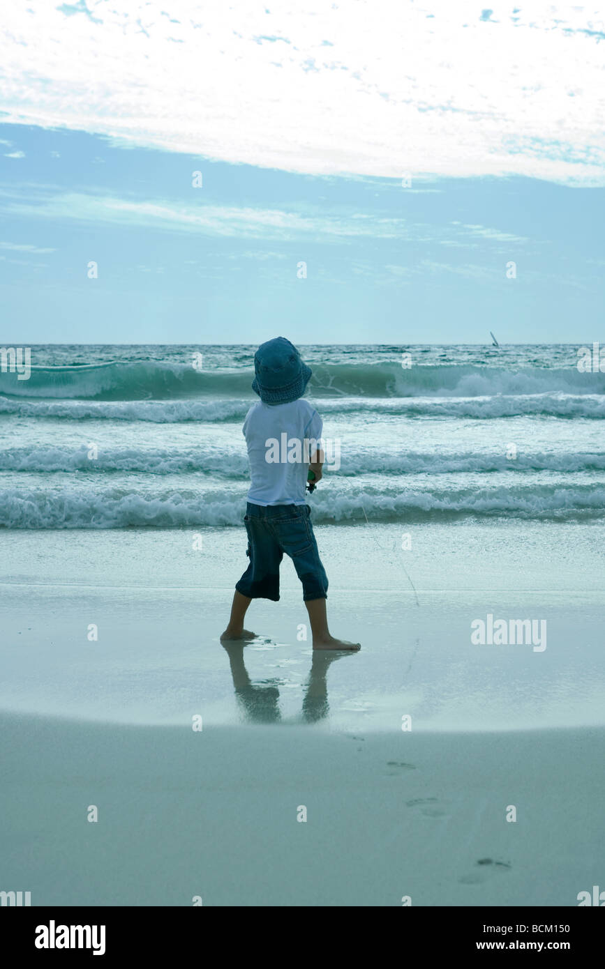 Boy holding fishing pole on beach, rear view - Stock Image