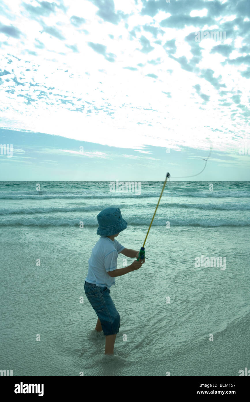 Boy throwing out fishing line on beach, rear view - Stock Image