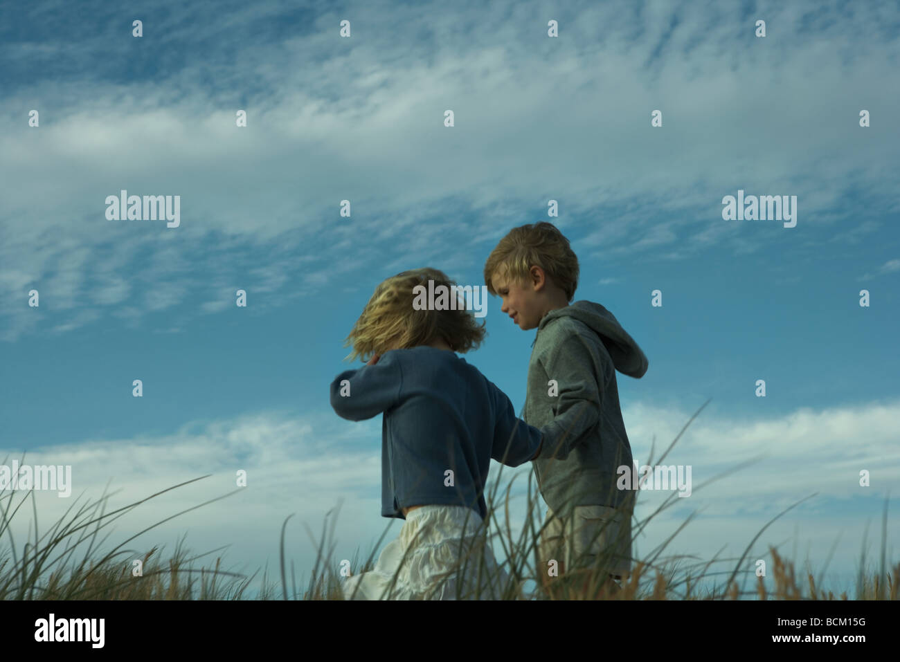 Boy and girl walking side by side through tall grass, holding hands - Stock Image