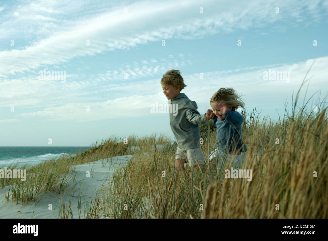 Boy and girl running through dune grass, holding hands - Stock Image
