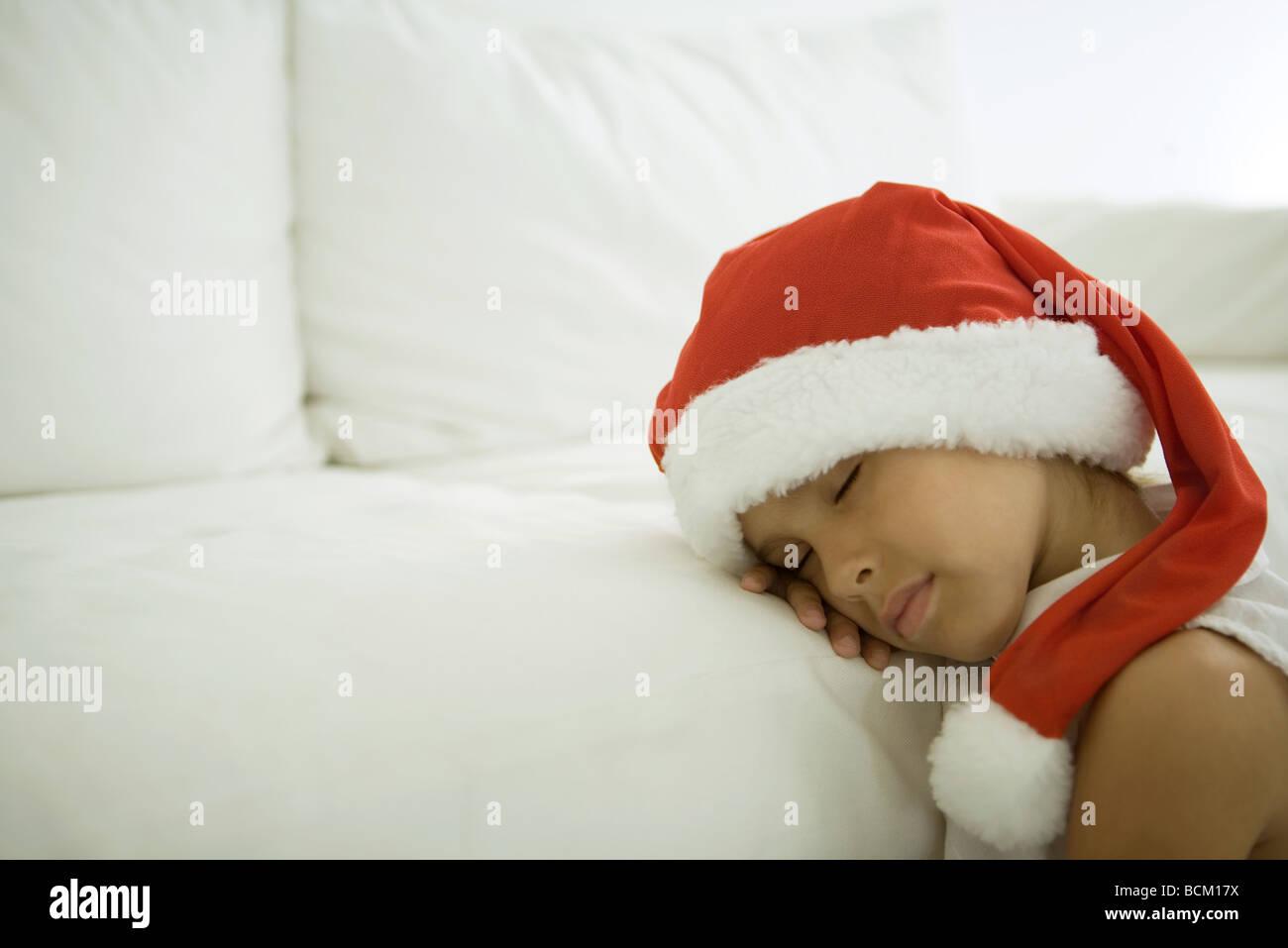 Child sleeping with head on sofa, wearing santa hat, close-up - Stock Image