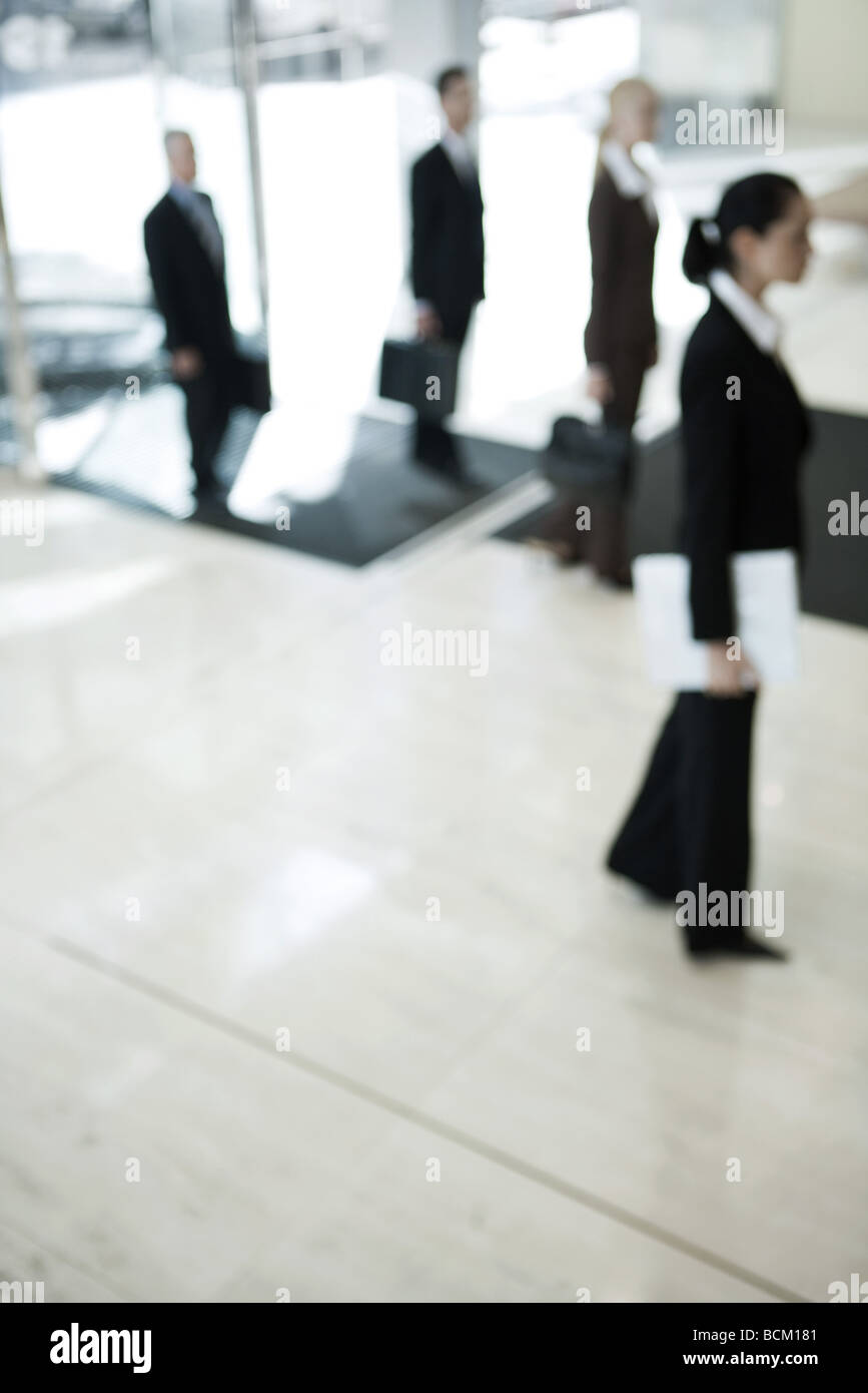 Business people entering lobby, side view, defocused - Stock Image