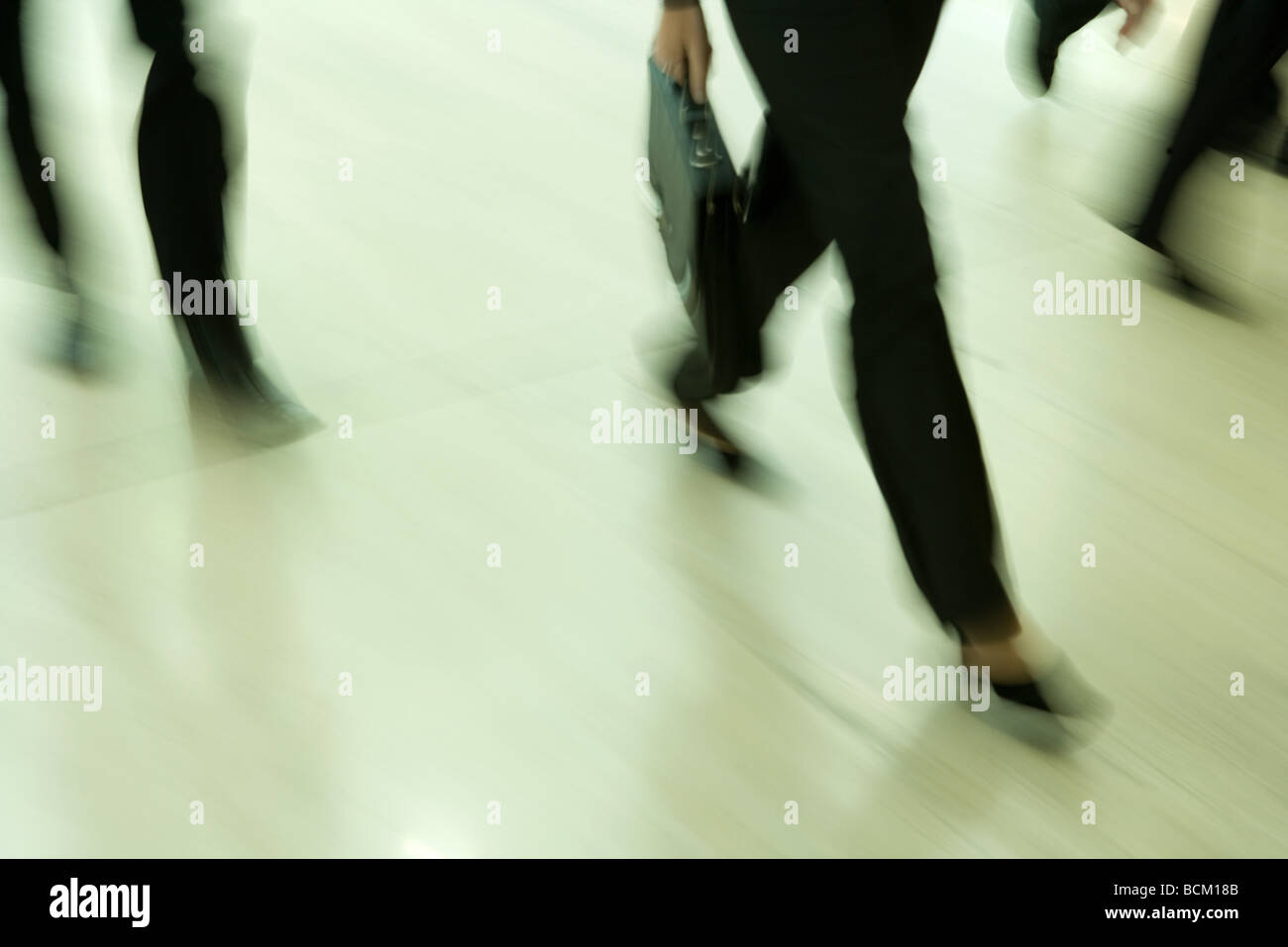 Business people walking, low section, blurred motion - Stock Image