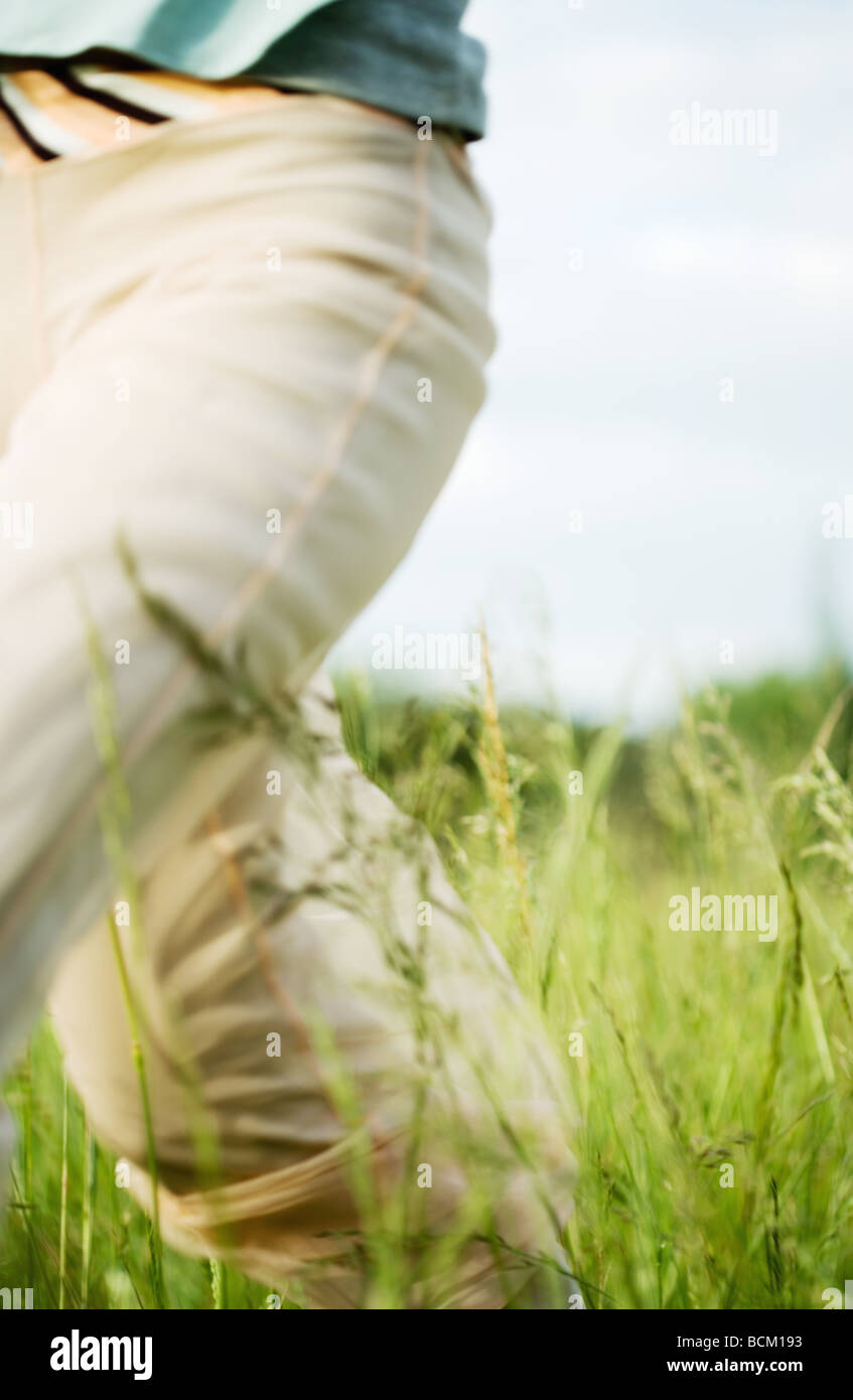 Woman walking through field, cropped view - Stock Image