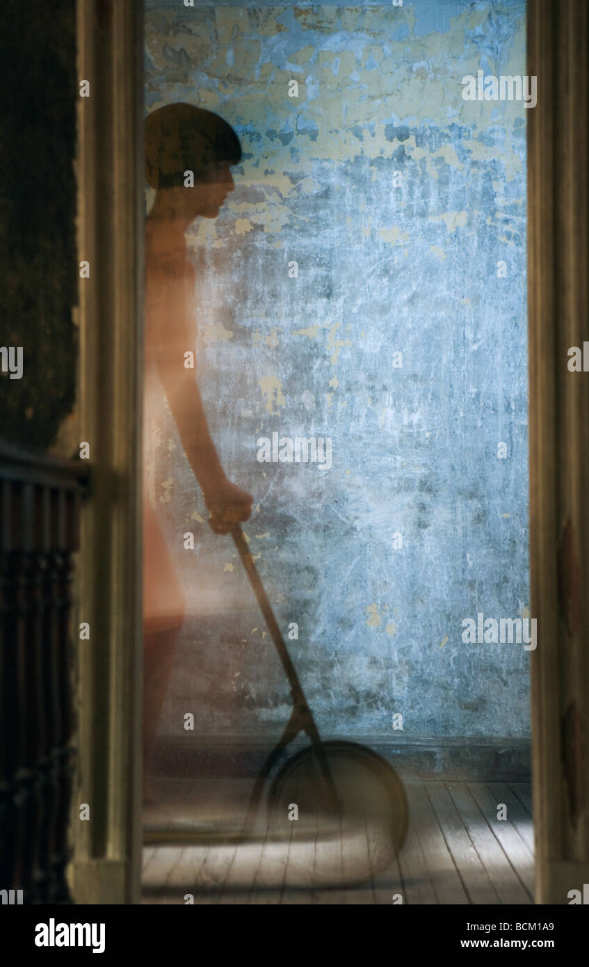 Woman riding scooter on hardwood floor, seen through doorway, blurred motion - Stock Image