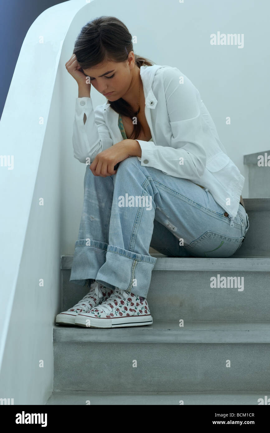 Teen girl sitting on stairs, holding head and looking down, full length - Stock Image