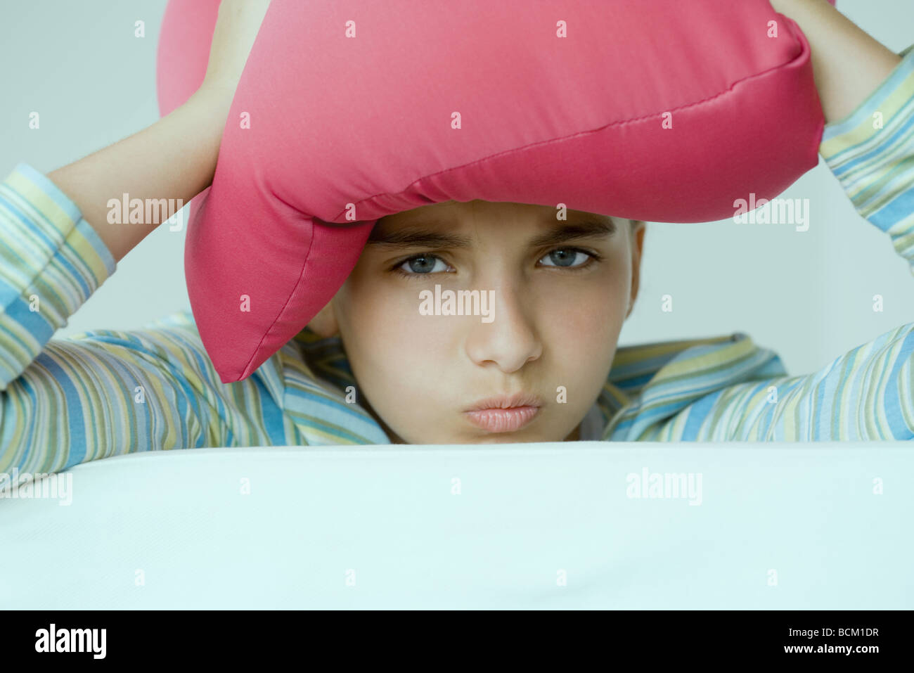 Preteen girl holding pillow on head, making faces at camera, close-up - Stock Image