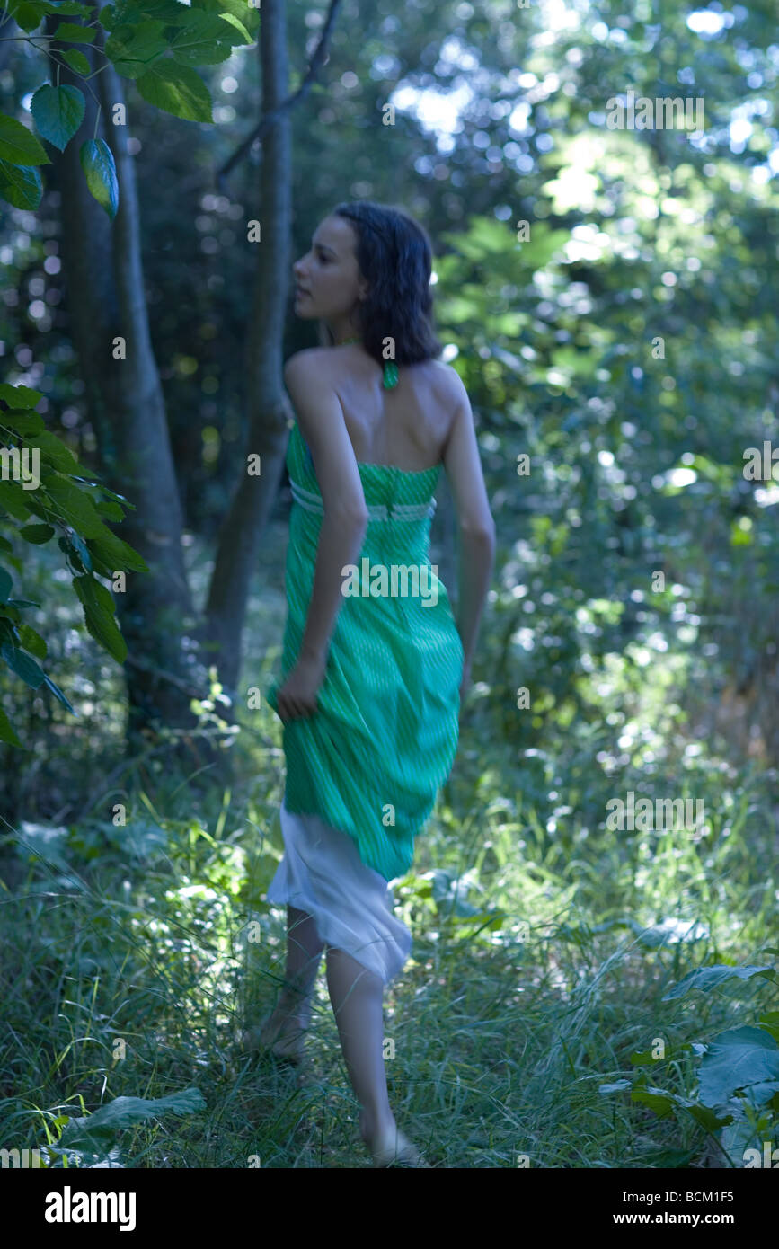 Rear view of young woman walking through forest, holding up bottom of dress, blurred motion - Stock Image
