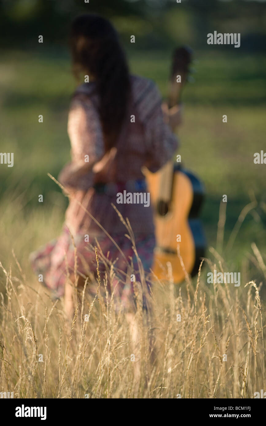 Rear view of woman walking through field, carrying guitar, focus on tall grass in foreground - Stock Image