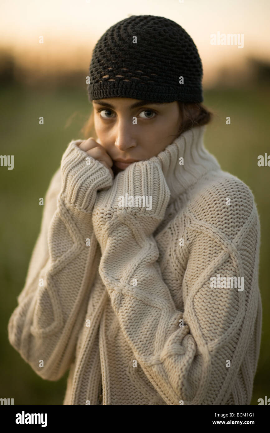 Woman standing outdoors wearing thick sweater, looking at camera, portrait - Stock Image