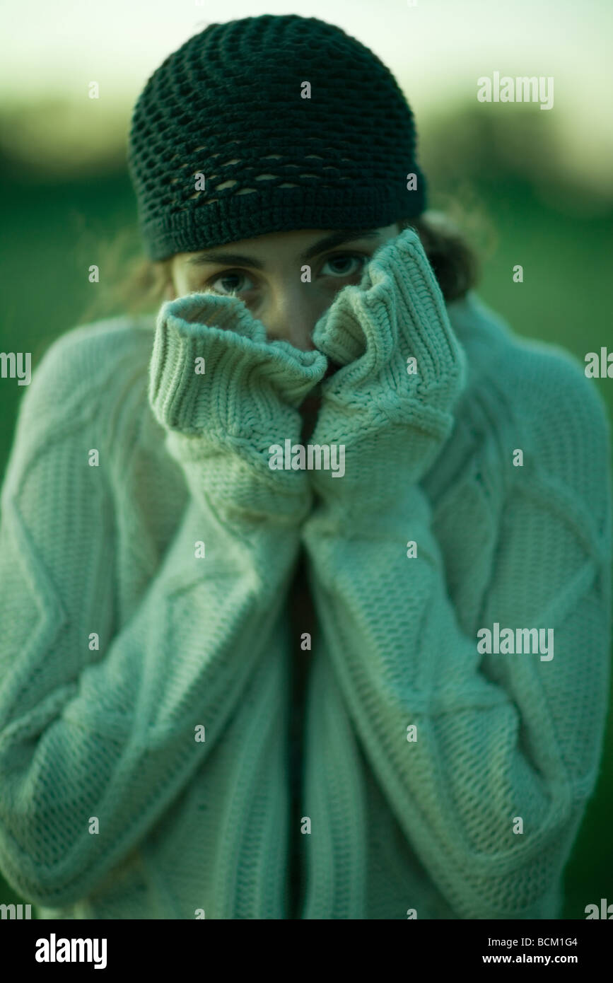 Woman wearing thick sweater, holding hands over mouth, looking at camera - Stock Image