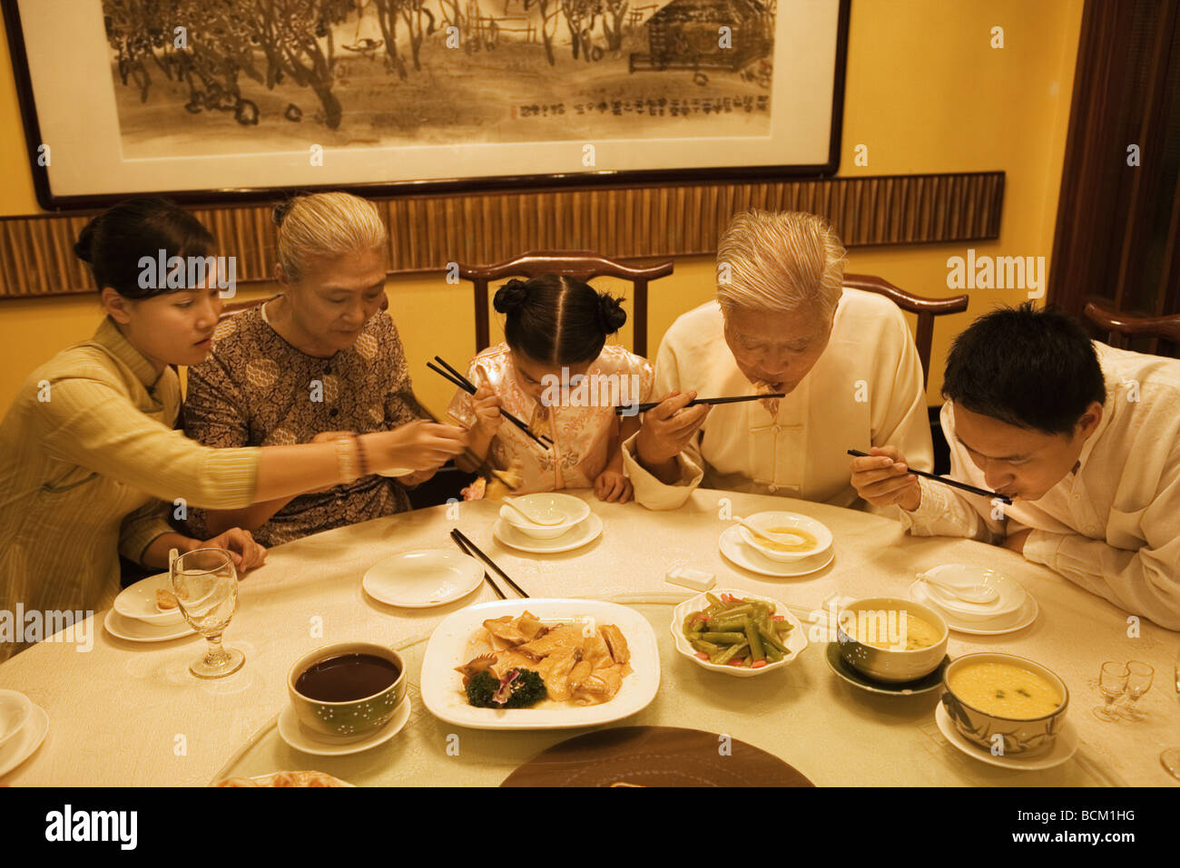 Three generation family eating meal with chopsticks, looking down Stock Photo