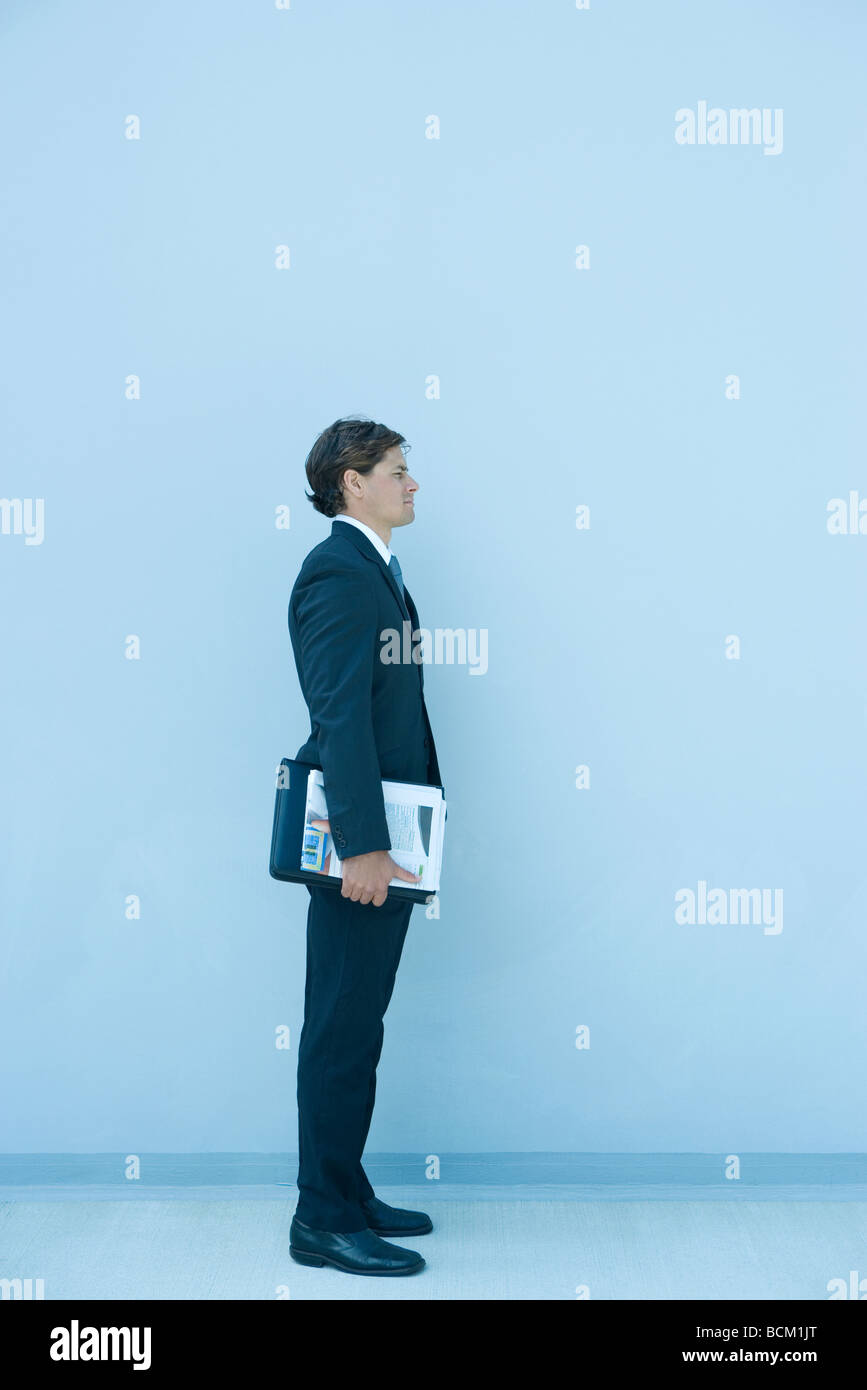 Businesman standing, holding binder under arm, full length - Stock Image