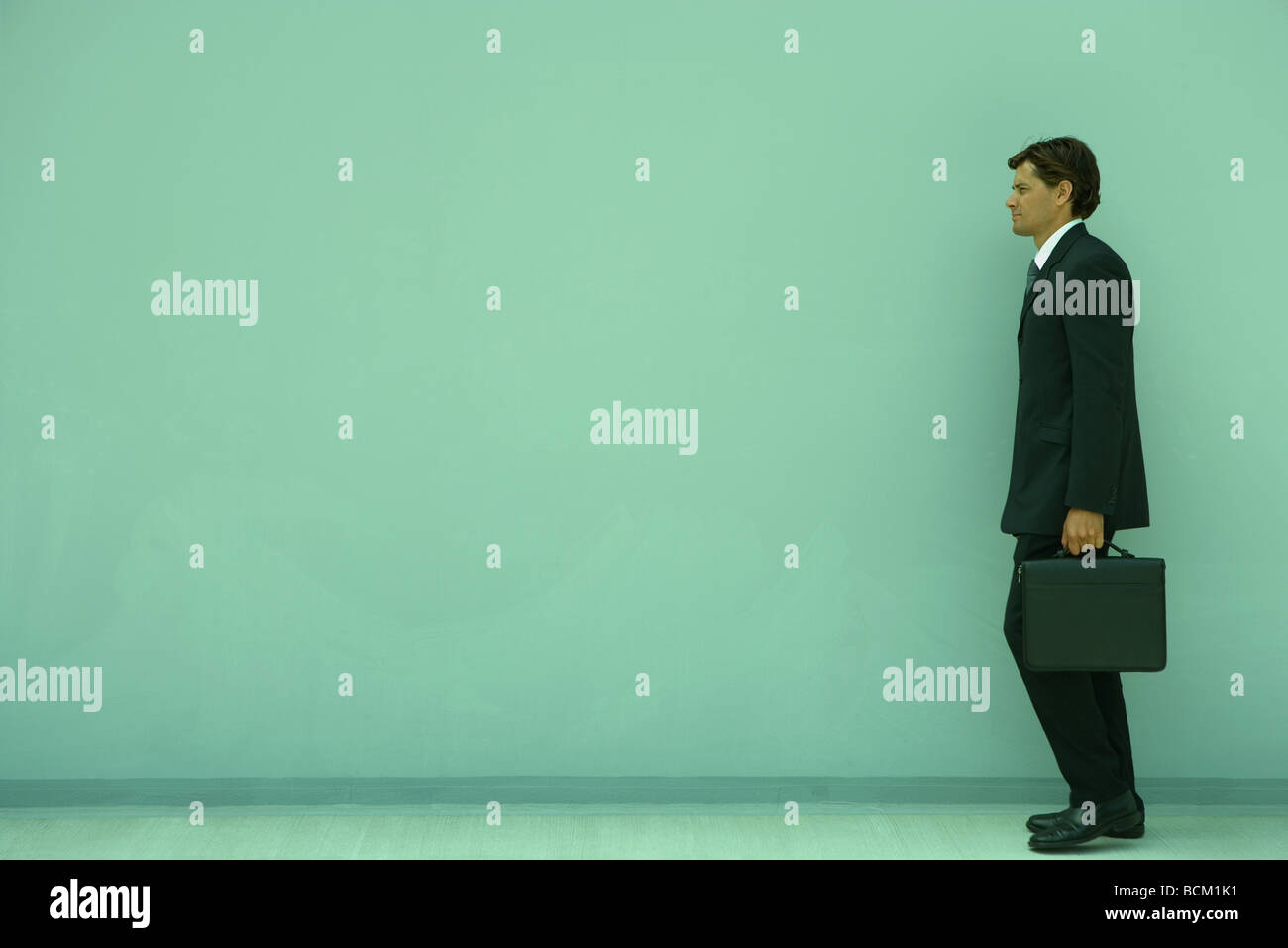 Businessman carrying briefcase, full length, side view - Stock Image