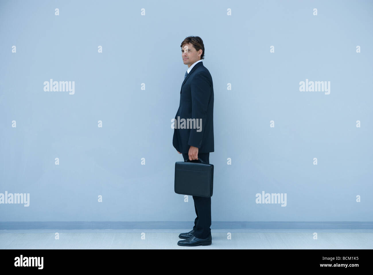Businessman standing, holding briefcase, full length - Stock Image