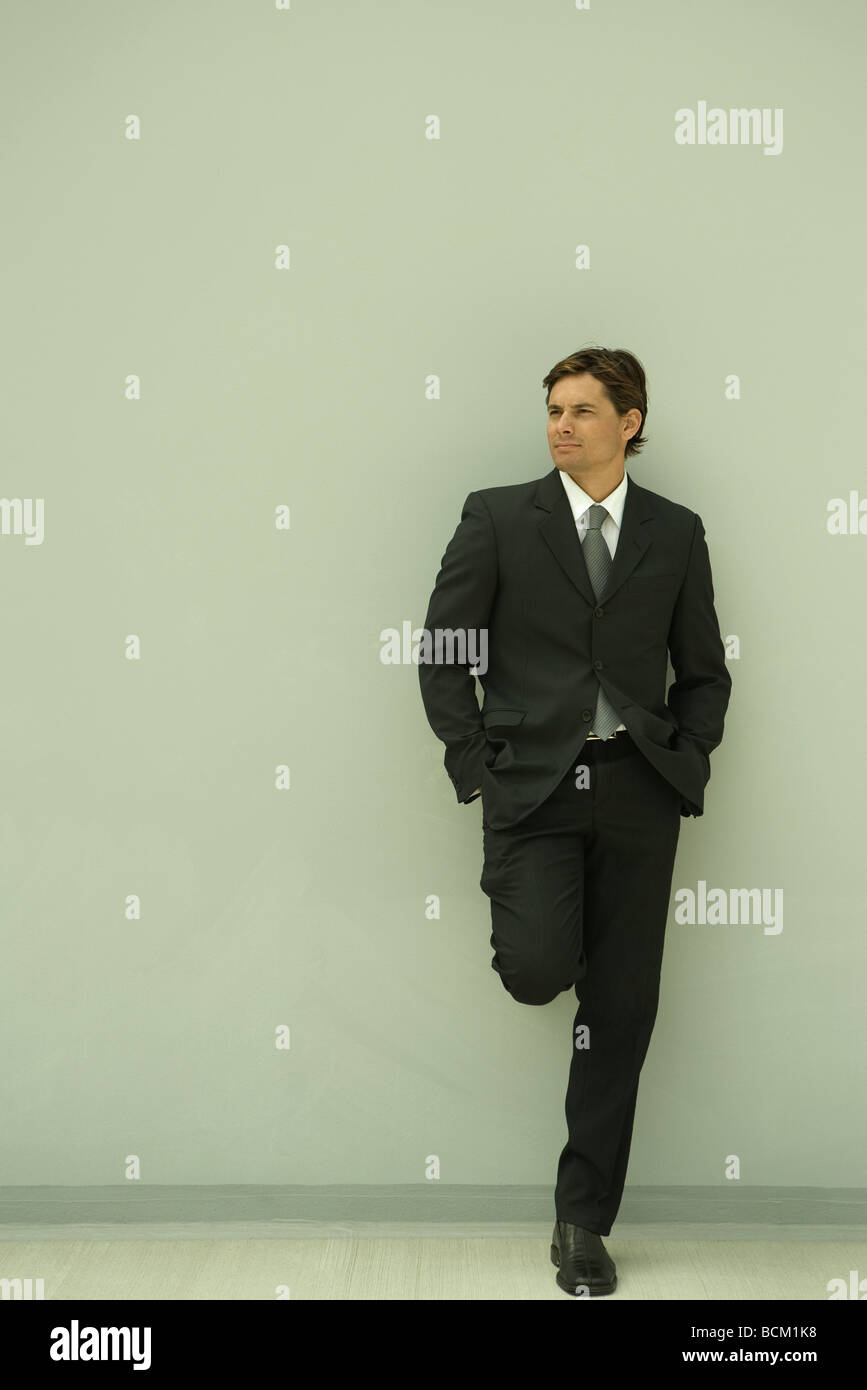 Businessman standing on one leg, leaning against wall with hands in pockets, looking away, full length - Stock Image