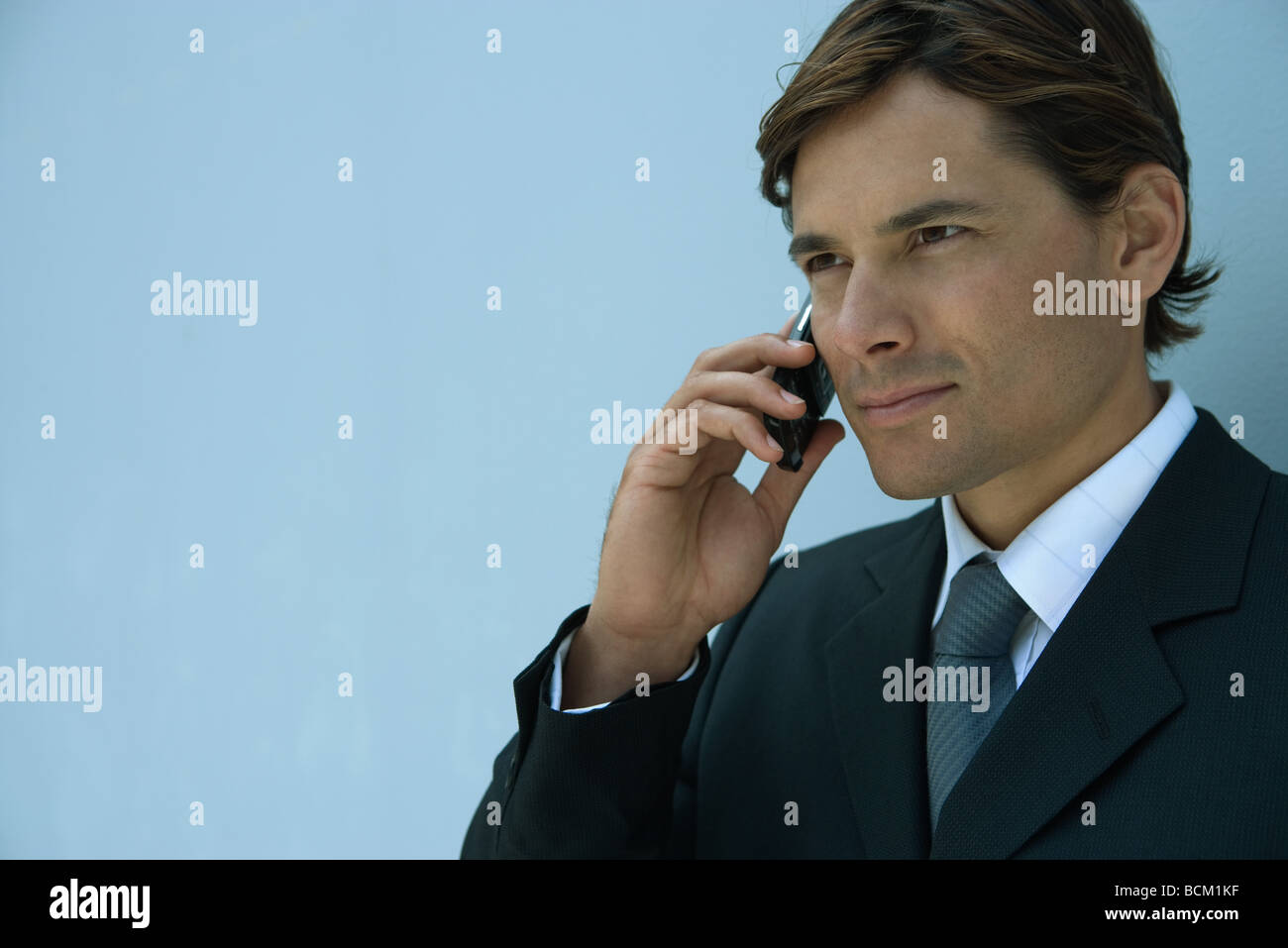 Close-up of businessman using cell phone, head and shoulders - Stock Image