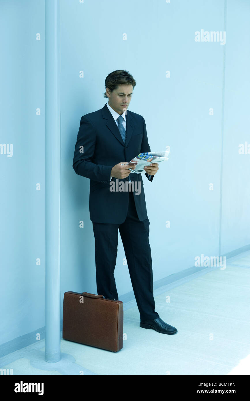 Businessman standing next to briefcase and reading newspaper - Stock Image