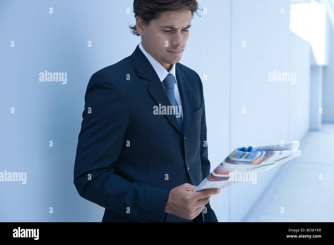 Businessman standing, reading newspaper - Stock Image