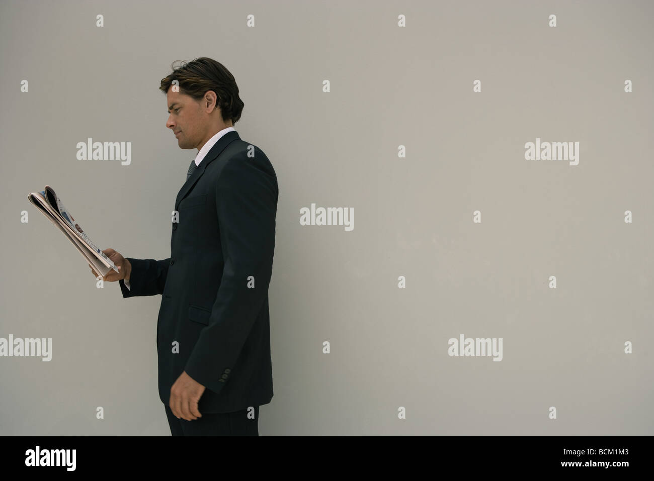 Businessman standing, reading newspaper, side view - Stock Image