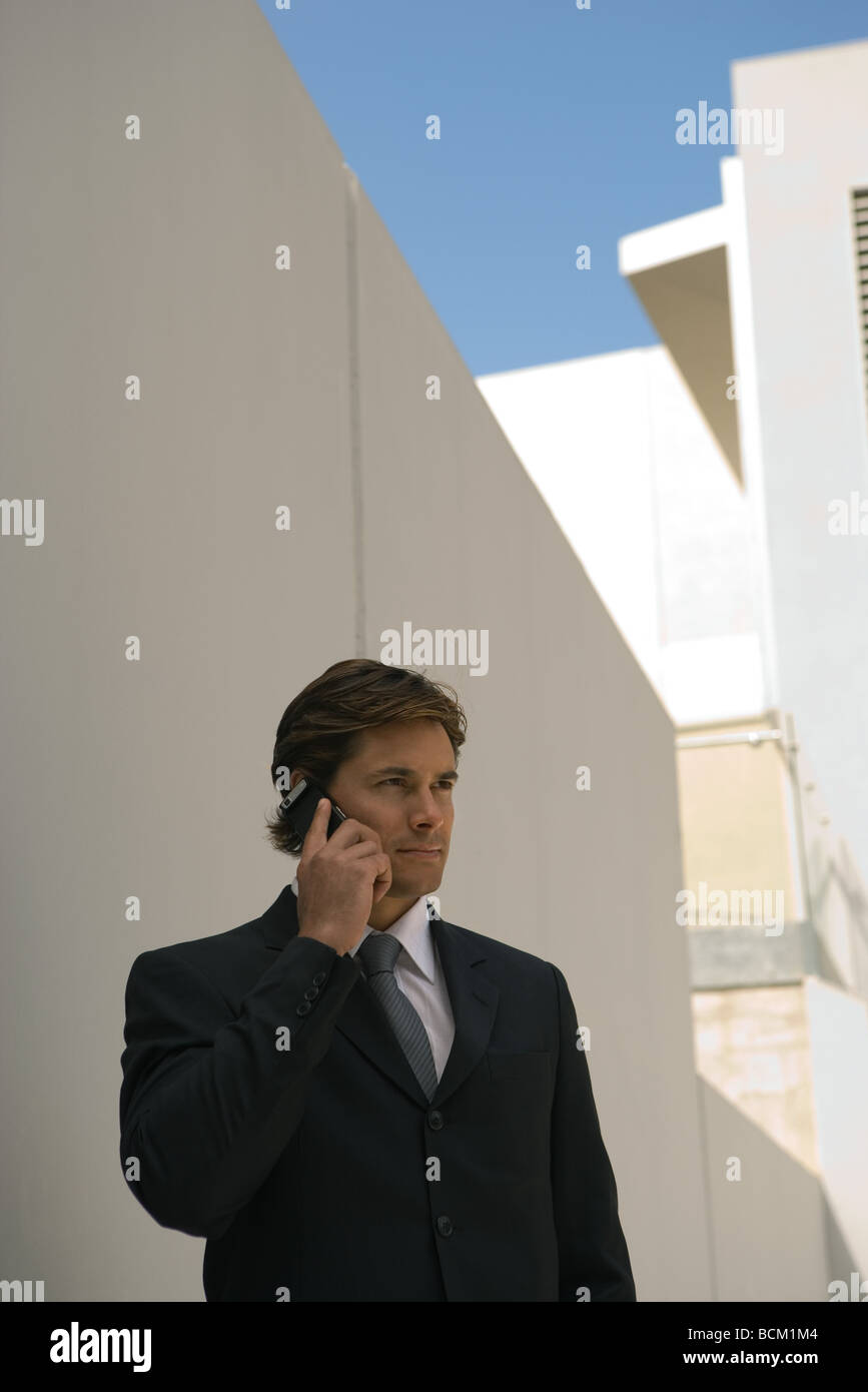 Businessman using cell phone, standing outdoors - Stock Image
