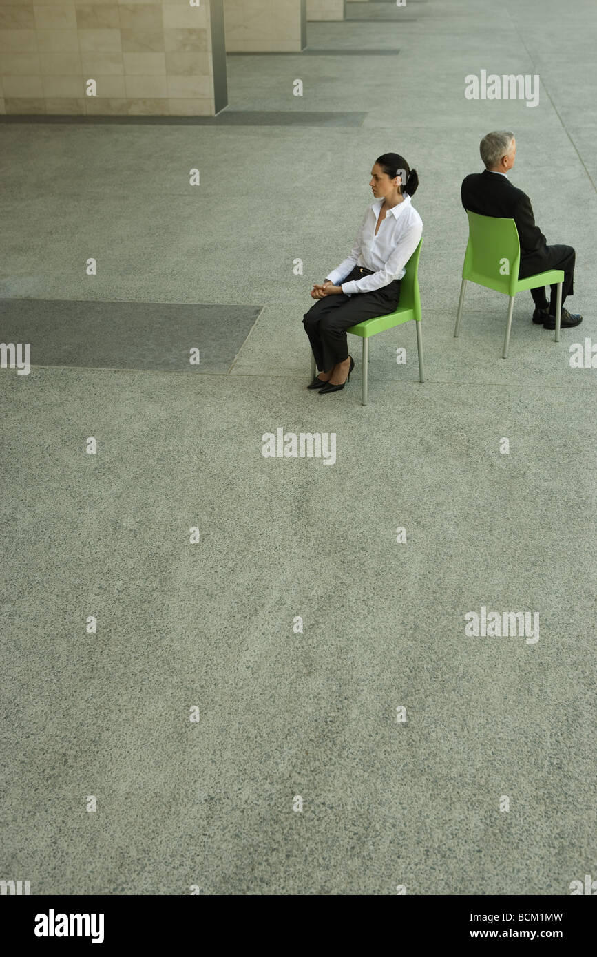 Businesswoman and businessman sitting back to back, high angle view, full length Stock Photo