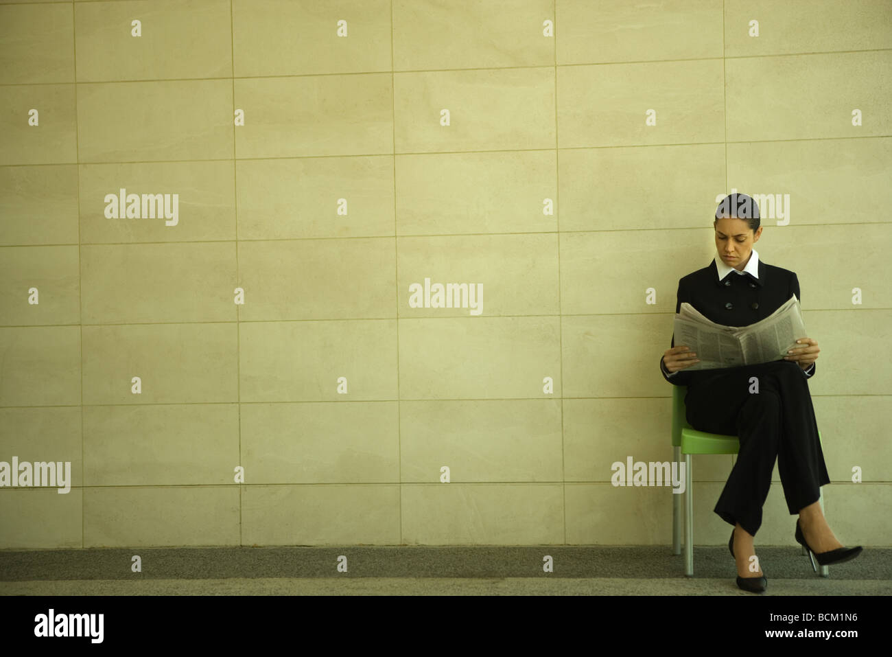 Businesswoman reading newspaper, sitting in front of tiled wall with legs crossed - Stock Image
