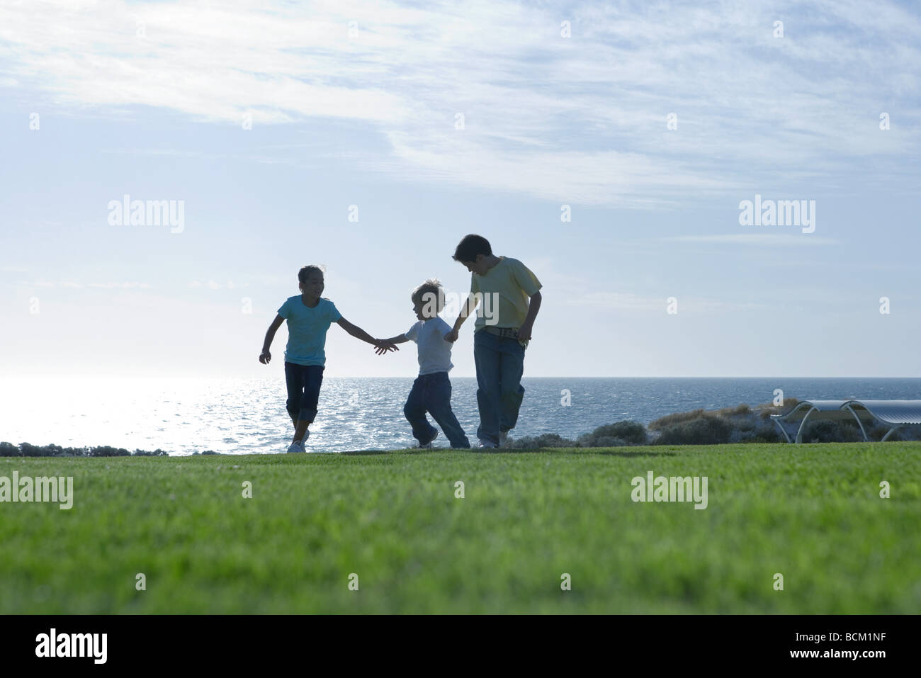 Three children running across grass, holding hands, sea in background, full length - Stock Image
