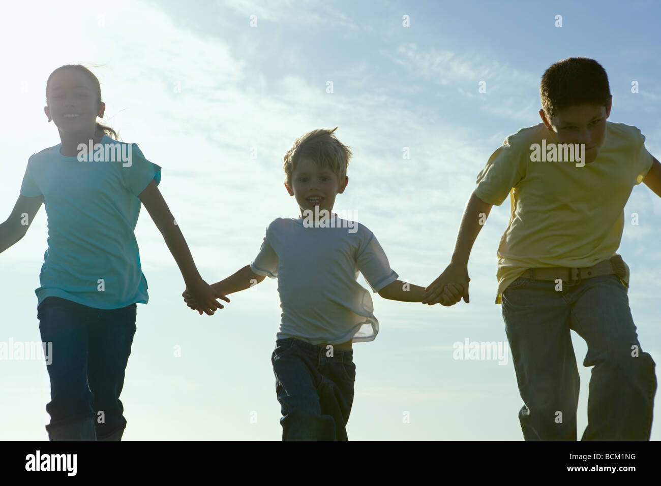 Three children running, holding hands, backlit - Stock Image