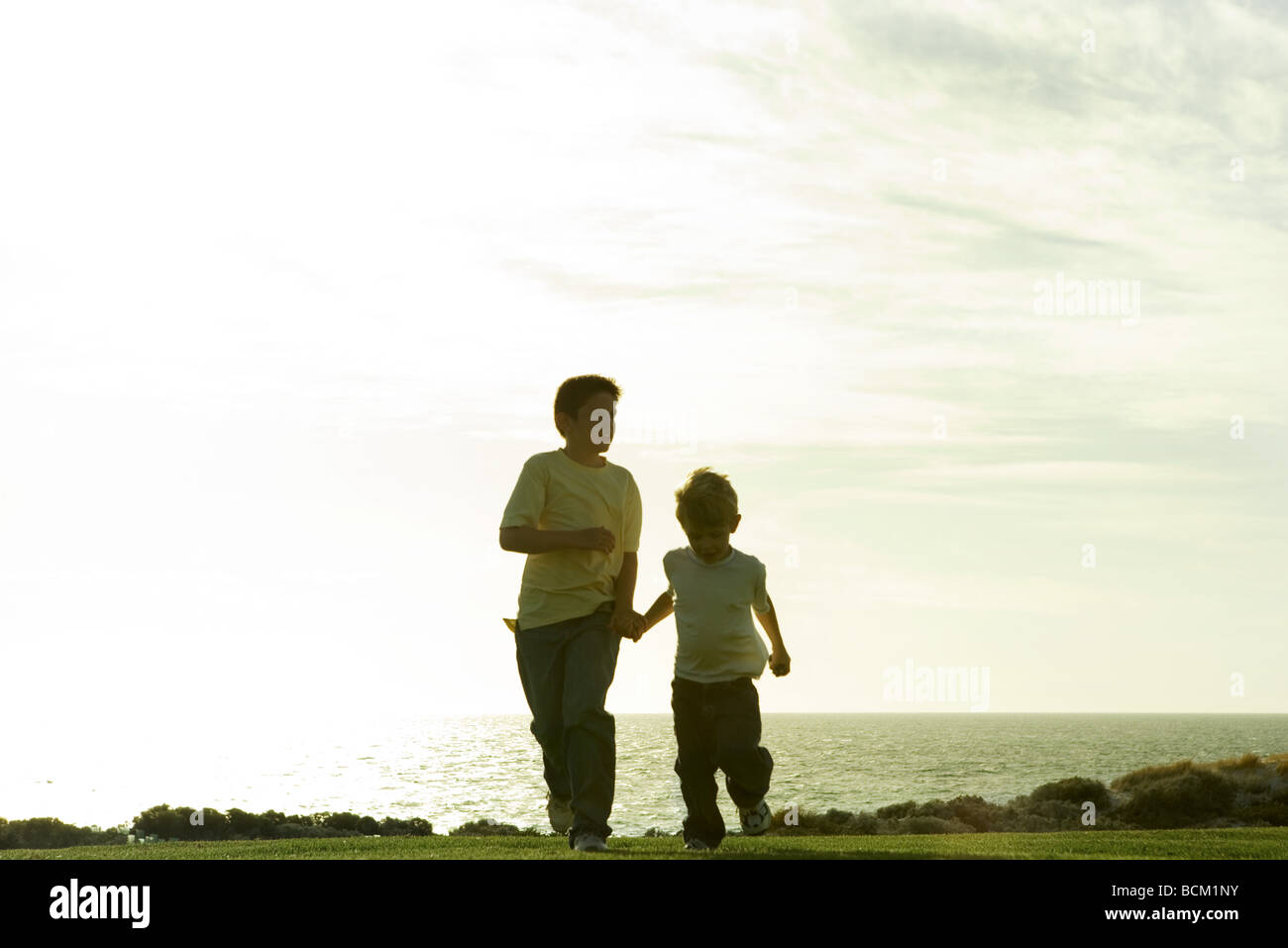 Two boys running and holding hands, ocean horizon in background - Stock Image