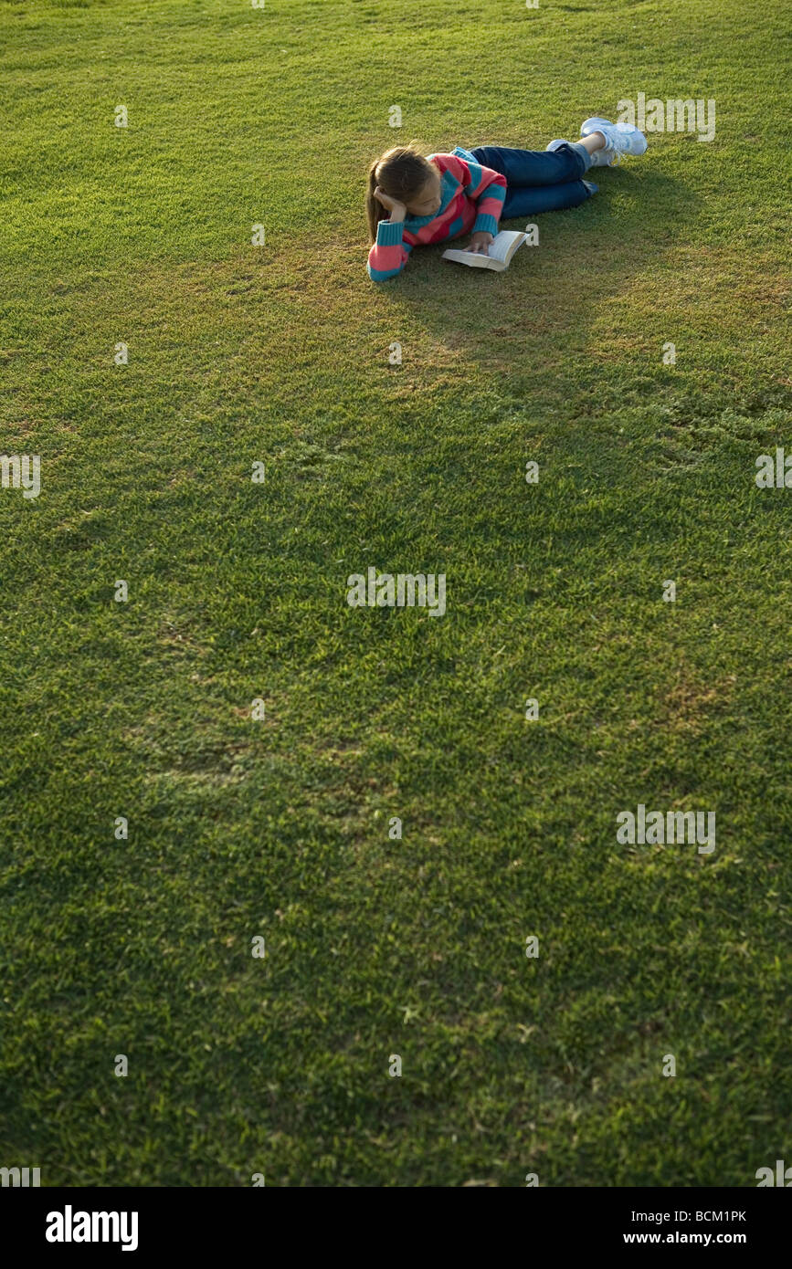 Girl lying on grass, reading book, full length - Stock Image