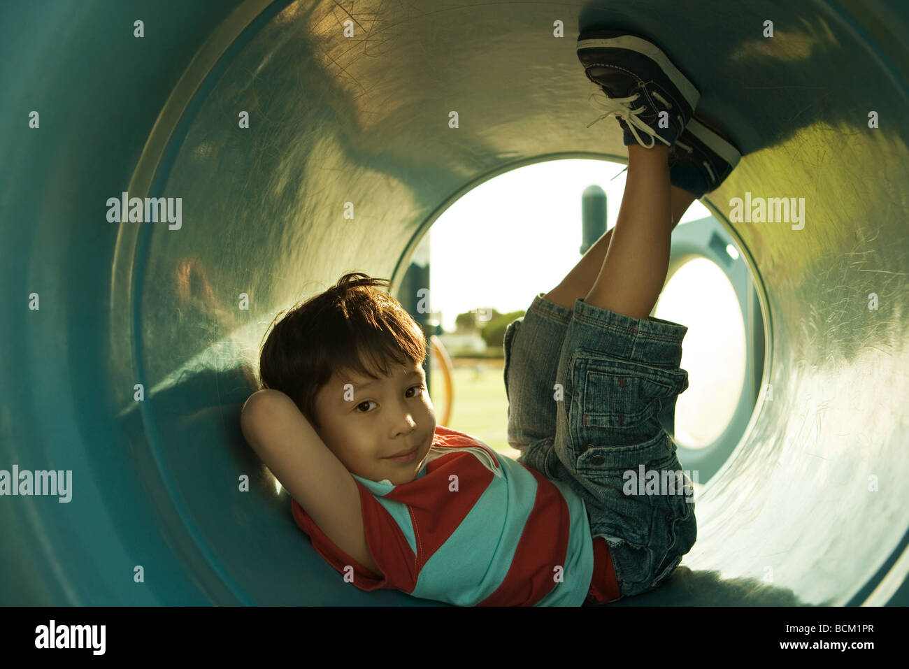 Boy sitting in playground tunnel with legs up, looking at camera, full length Stock Photo