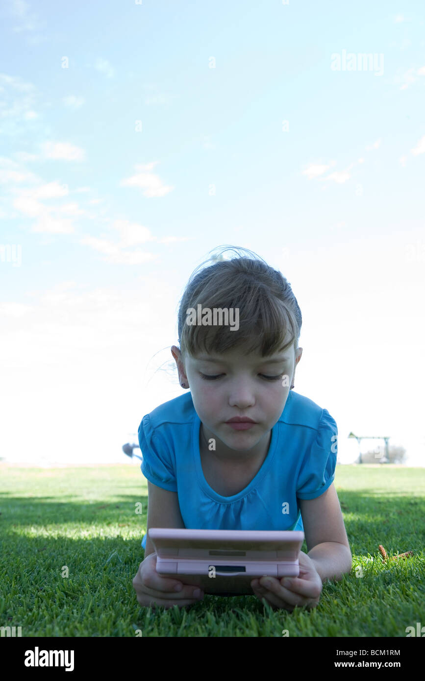 Girl lying on grass, playing with video game, front view Stock Photo