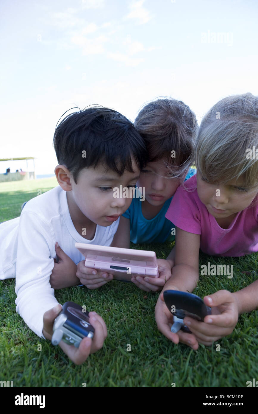 Three children lying on grass, playing with video game, holding cell phones, close-up Stock Photo