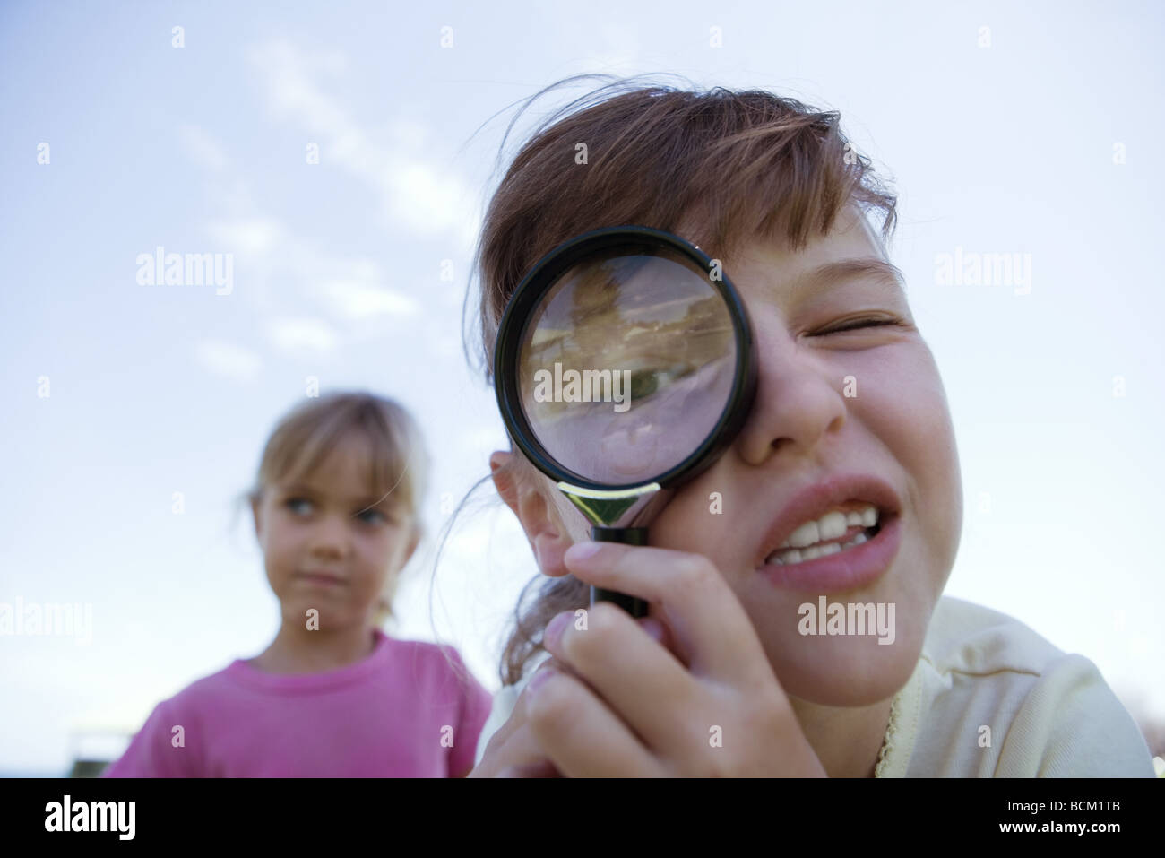 Girl looking through magnifying glass, looking at camera, close-up - Stock Image
