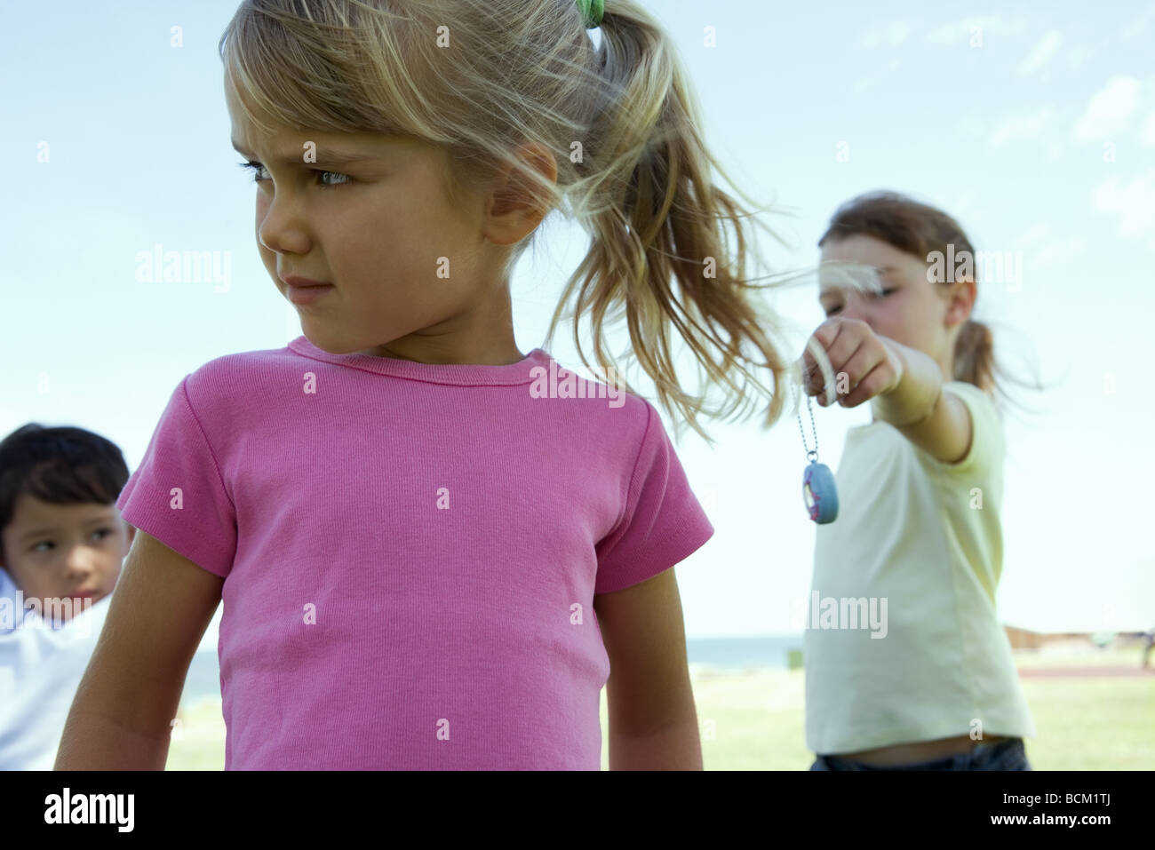 Three children outside, girl in foreground turning head while girl in background holds out toy to her - Stock Image