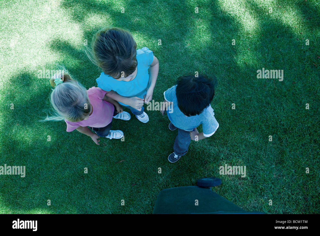 Three children standing on grass, in shade, view from directly above - Stock Image