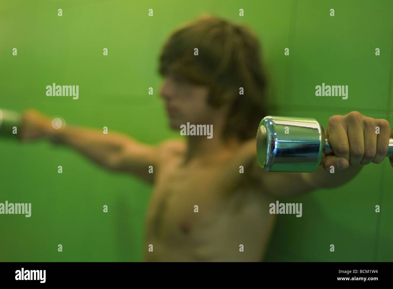 Young man holding dumbbells out to side, side view, focus on foreground Stock Photo