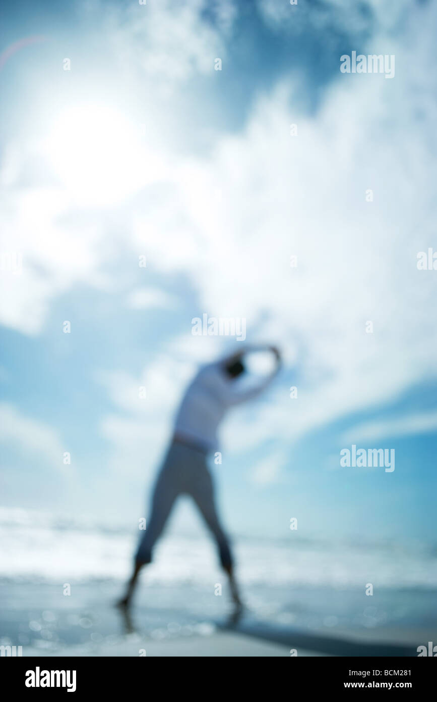 Person standing at the beach, arms raised, rear view, defocused - Stock Image