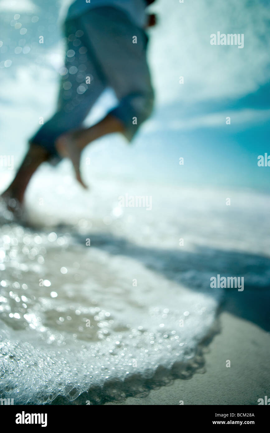 Person running at the beach, low angle view, cropped - Stock Image
