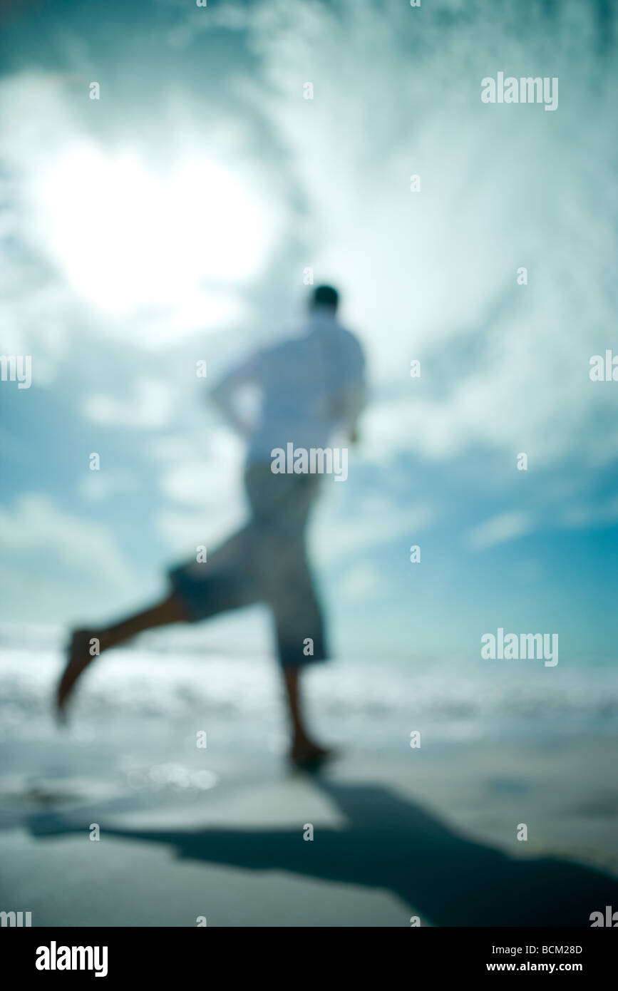 Person running at the beach, low angle view, defocused - Stock Image