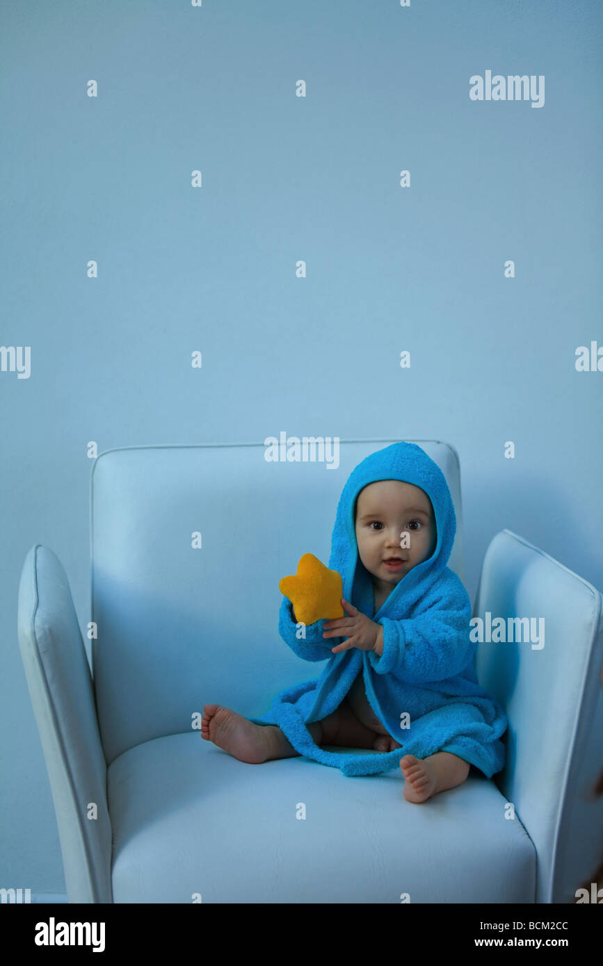 Baby boy wearing hooded bathrobe sitting in armchair, holding stuffed toy, looking at camera - Stock Image