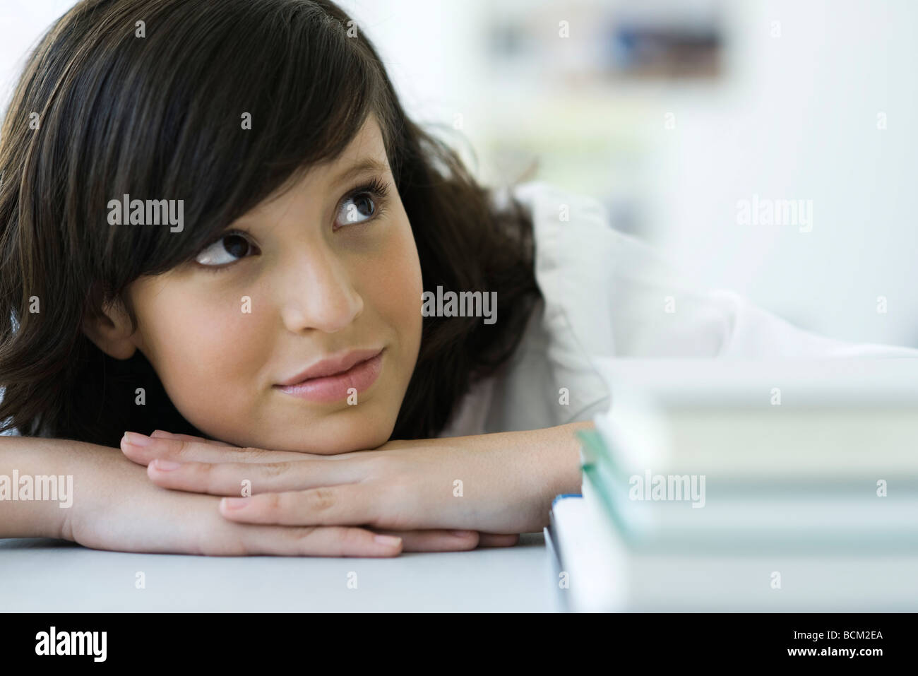 Young female resting head on hands, looking up dreamily, stack of books in foreground - Stock Image