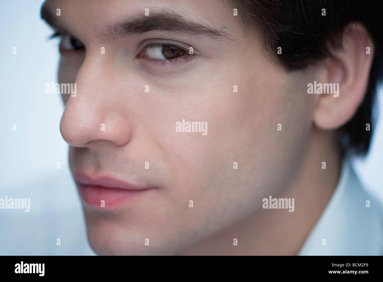 Young man glancing sideways at camera, close-up - Stock Image