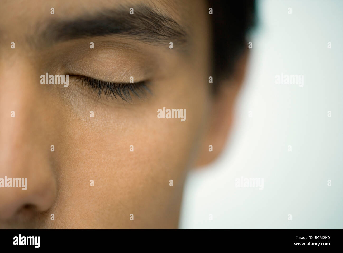 Man with eye closed, extreme close-up - Stock Image