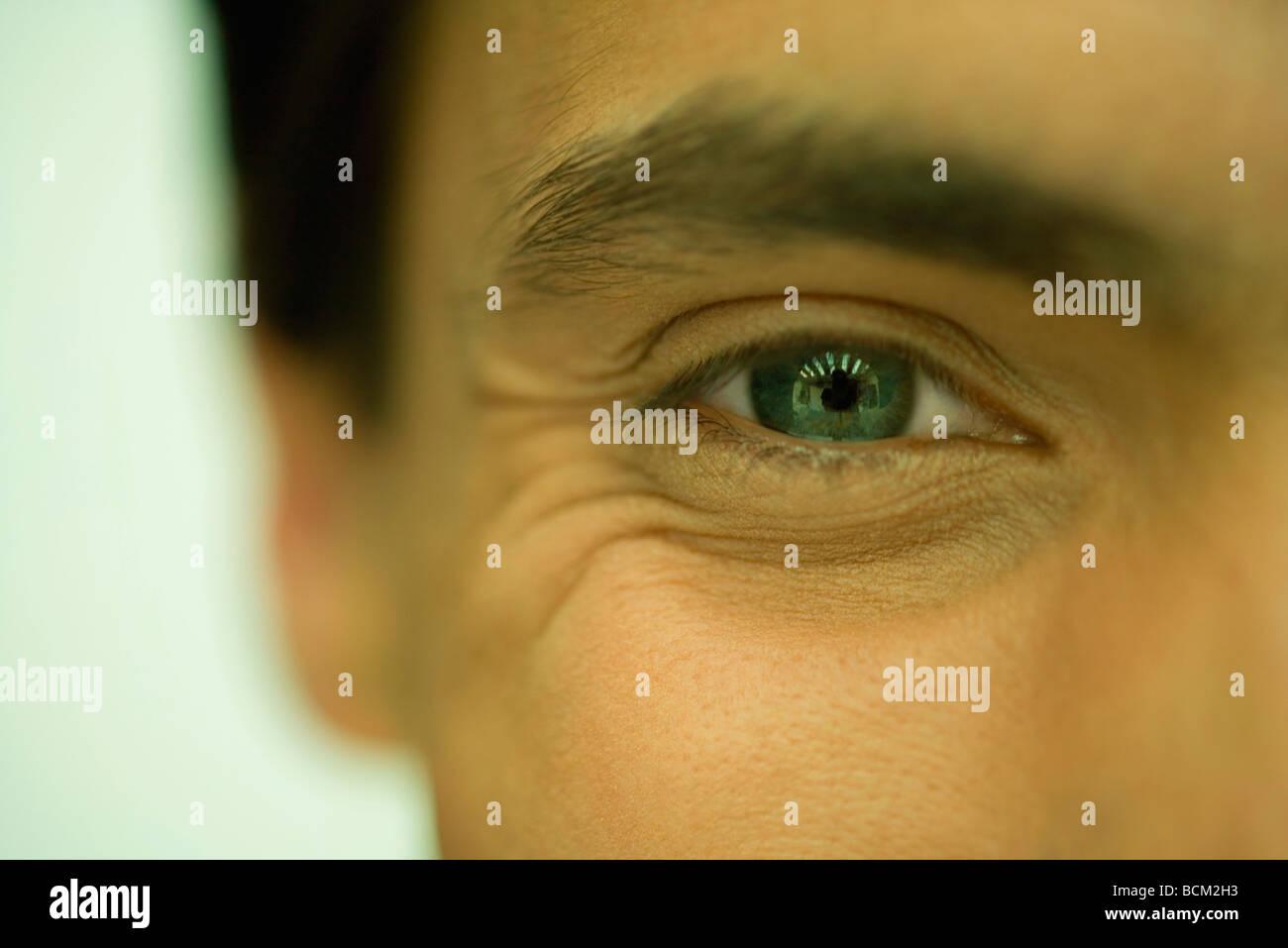 Man looking cheerfully at camera, cropped view of eye - Stock Image