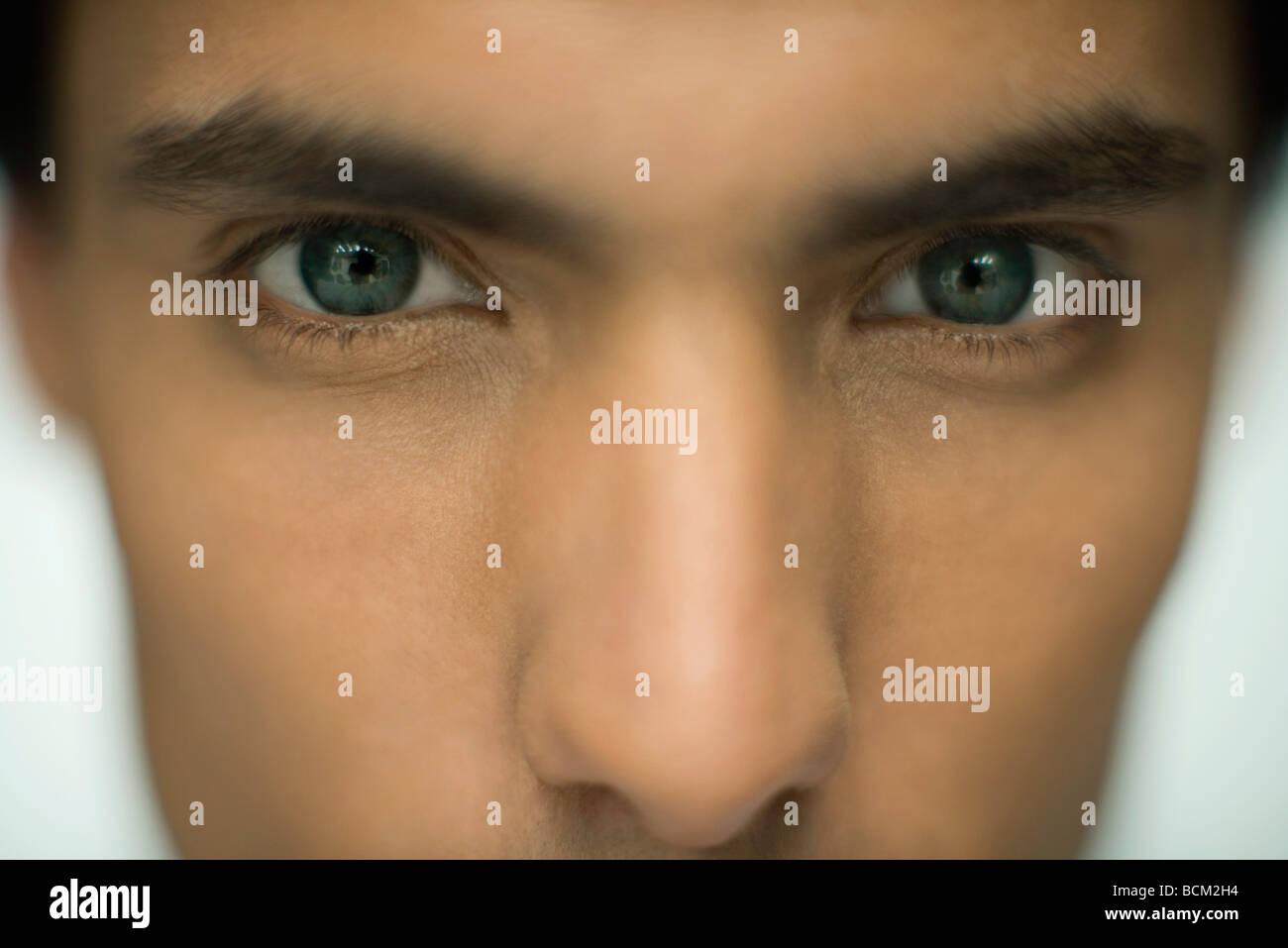 Man staring at camera, extreme close-up - Stock Image