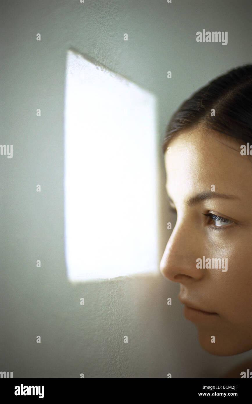 Woman peeking out small window, close-up - Stock Image