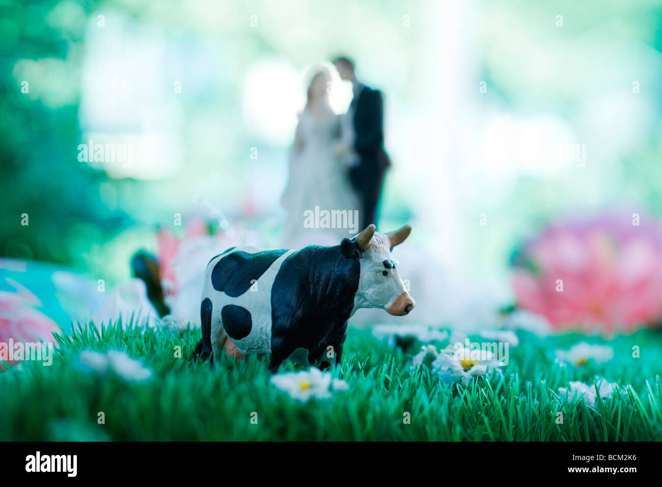 Plastic cow standing in field of fake flowers - Stock Image